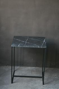 A modern steel and marble side table