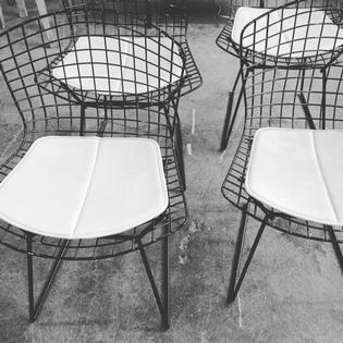 A set of 4 black metal Bertoia chairs with original leather cushions